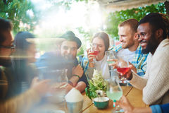 Restful people. Cheerful guys and girls spending time in outdoor cafe Royalty Free Stock Photo