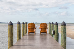 Restful Place. Adirondack chairs on a wooden pier in the tropics Stock Photography