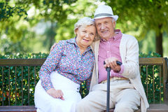 Restful seniors. Happy seniors sitting on bench in the park and enjoying rest Royalty Free Stock Image