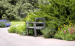 Restful Sitting. A bench in the middle of country living with greenery and flowers Royalty Free Stock Photography