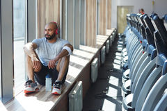 Restful sportsman. Looking through window during rest after workout Stock Photos