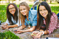 Restful students. Positive teenage girls with telecommunication technologies looking at camera in park Royalty Free Stock Photo