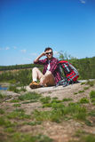 Restful tourist. Young hiker with backpack sitting by lake Royalty Free Stock Image