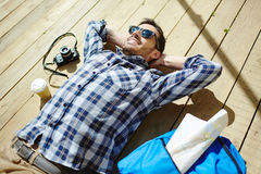 Restful traveler. Young man relaxing on sunny day Stock Photos