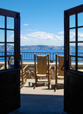 Restful Vista on Sunny Porch. Rocking chairs on sunlit deck overlooking Crater Lake Stock Photography