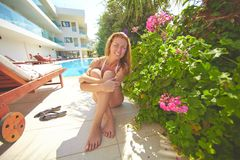 Restful woman. Female sunbather sitting by pool at resort Royalty Free Stock Image