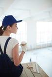 Restful worker. Happy young painter in uniform having coffee break Stock Images