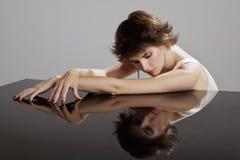 Resti affascinanti della giovane donna su surfac rispecchiato fotografia stock