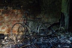 Resti bruciato-fuori della bicicletta nella casa bruciata Immagine Stock