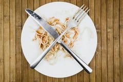 Resti degli spaghetti, della forcella e del coltello su un piatto bianco fotografie stock
