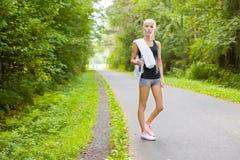 Resti del corridore della donna dopo l'allenamento all'aperto Fotografia Stock