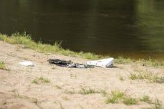 Resti di un falò sulla spiaggia vicino al lago Il contenitore di pizza si trova sulla sabbia contro lo sfondo dell'acqua fotografia stock