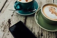 Resti verdi e blu del caffè e dello smartphone della tazza su una tavola di legno Immagine Stock