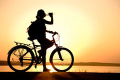 Resting. Silhouette of the girl on a bicycle, drinking water with beautiful lake near by at sunset Royalty Free Stock Photos