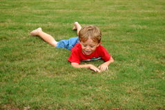 Resting. A young boy lying in the grass after running really fast Royalty Free Stock Images