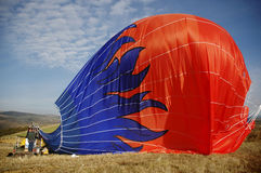 Beautiful Hot Air Balloon with Blue Flames, Deflating on Ground Royalty Free Stock Image