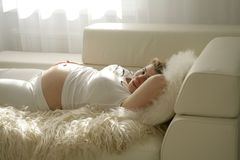 Resting. Pregnant woman laying in bed with one hnd holding belly Stock Photography