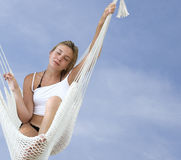 Resting. Young blond woman resting in a hammock on a blue sky background Royalty Free Stock Photo