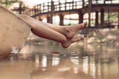 Resting adventurer. Female feet with anchor tattoo hanging out of boat royalty free stock photography