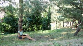 A resting base in the woods, the girl reads a book sitting on a lawn under a tree stock footage