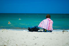 Resting on the beach. Woman in colourful beach towel resting on the seashore, photographed from the back Stock Image