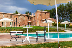 Resting. A beautiful and luxurious tuscany swimming pool with parasols and chairs Stock Photos