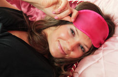 Resting Beauty. Beautiful girl in bed peeps out from under the mask for sleeping Royalty Free Stock Images