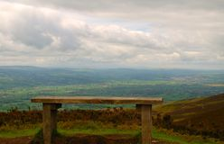Resting Bench. Wooden bench on a mountain walk with a great view over the countryside below,with rolling clouds and patches of blue sky Stock Image