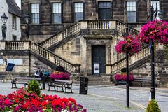 The Town House in Linlinthgow, Scotland, UK, Summer, 2018. Resting on the bench in front of a historical building, the Town House in Linlinthgow, Scotland, UK royalty free stock photography