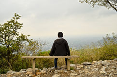 Resting on a bench. A young boy resting on a bench on a hill facing towards the city stock photo