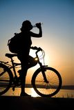 Resting bicycler. Silhouette of the girl on a bicycle, drinking water with beautiful lake near by at sunset Stock Images