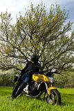 Resting biker. Biker with a sport motorbike resting against a nature calm landscape with a blue cloudy sky stock image
