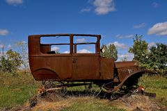 Rusty frame of a very old car. Resting on blocks is the rusted frame of a very old car Stock Photography