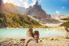 Resting with boots legs crossed near Lago di Sorapis, Dolomites, Italy with blue sky, azure water and high mountains in the stock images
