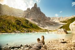 Resting with boots legs crossed near Lago di Sorapis, Dolomites, Italy with blue sky, azure water and high mountains in the stock image