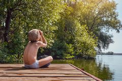 Resting boy near river. Little boy on the pier having rest and looking on sun Stock Photos