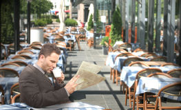 Resting businessman drinking coffee and reading newspaper in the restaurant stock images