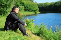Resting businessman sitting on river bank Stock Photography