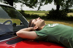 Resting on a car. Cool guy resting on the bonnet of his car royalty free stock images