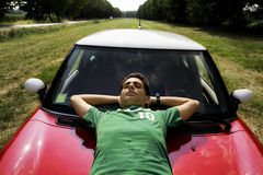 Resting on a car. Cool guy resting on the bonnet of his car royalty free stock photos