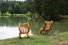 Resting chairs made of wood by the lake Royalty Free Stock Image