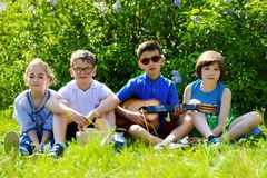 Resting cheerful children. Group of cheerful children resting in the park with songs and guitar. Outdoor activity. Summer holidays Stock Image