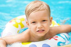 Resting child. Wet boy swimming in an inner-tube resting by the board of the swimming pool Stock Images