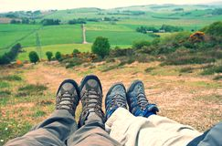 Resting child and adult feet after hill walk. Adult and Child lying their feet on the countryside hill with walking shoe and green fields in the background Stock Photography