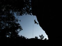 Resting climber silhouette. Silhouette of woman climber resting while climbing an overhanging cliff framed by the cliff and trees Stock Photo