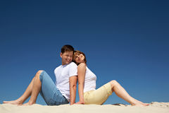 Resting couple. Portrait of relaxing couple sitting back to back on sandy beach against blue sky Stock Photography