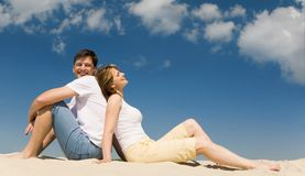 Resting couple. Portrait of relaxing couple sitting back to back on sandy beach against blue sky Stock Photos
