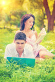 Resting couple with laptop and book in park on grass instagram c Stock Photo