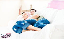 Resting couple lying on sofa after painting a room Royalty Free Stock Photo