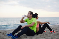 Resting couple of two runners sitting on the beach Stock Photo